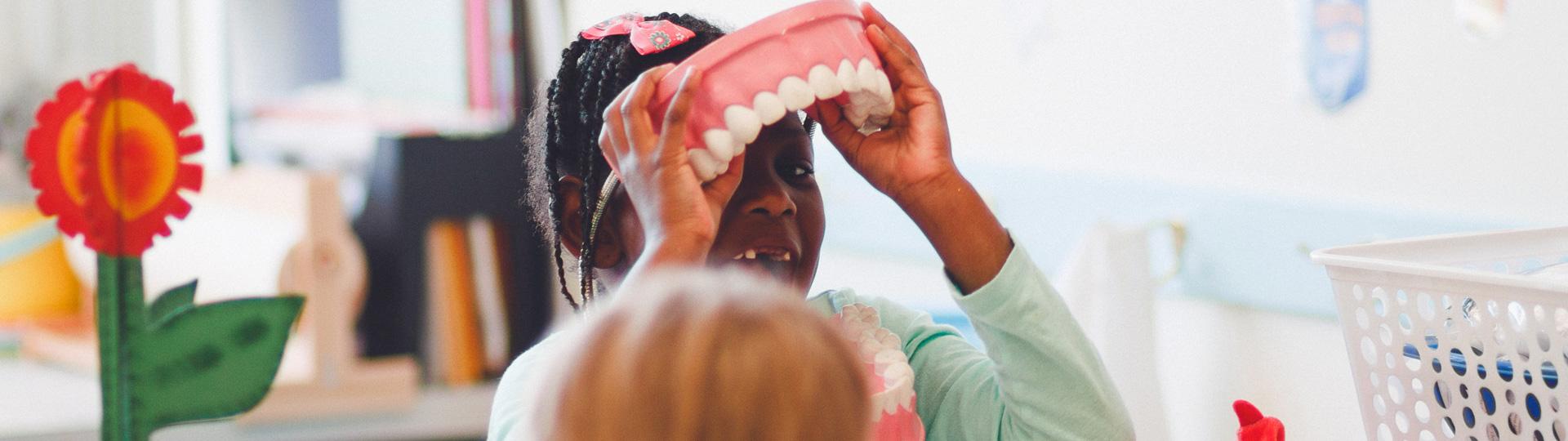 Girl wearing giant teeth for fun